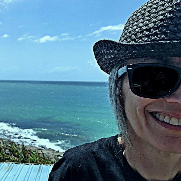Alice wearing a hat and sunglasses, smiling at the beach