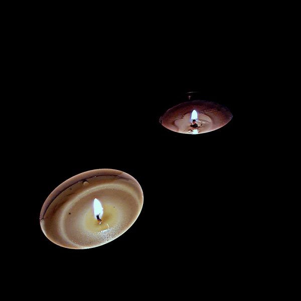 two candles lit in the dark